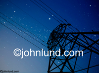 A high tension power pylon silhouetted against a deep blue sky filled with stars. Picture of powerlines.
