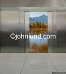 Stock photo of open elevator doors revealing the still waters of a lake with trees and mountains in the distance. Elevator pics. The interior of the elevator is stainless steel.