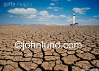 Picture of a lighthouse surrounded by dry cracked land and dry cracked earth,  illustrating ecology issues, global warming and conservation