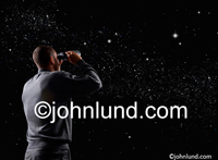 Man at night observing the stars through binoculars in a photo about discovery, exploration and seeking. The man's back is to the camera.  Picture of night sky full of starts.  Starfield pics.