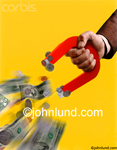 Picture of a big magnet attracting money.  The money magnet is being held by a business mans hand. The background is yellow. The Magnet is drawing in paper money and coins.