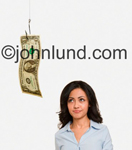 Stock photo picture of a pretty Hispanic woman being tempted by a dollar on a fish hook. She is looking up at the money on the fishing hook and getting ideas. Money being used for bait.