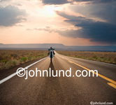 Stock photo of a lone motorcyclist approaching at sunset down a long straight highway symbolizing freedom and a journey. Pictures of motorcycle riding.