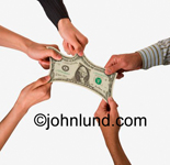 Stock photo of multiple hands stretching a dollar bill. The dollar is being stretched in several directions at once. Represents tight budgets, cost cutting, penny pinching and other concepts.
