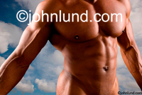 A body builders amazingly well muscled nude torso against a dramatic cloudscape showing strength, power and vitality.