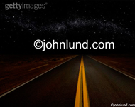 Stock shot of a long road stretching into the night and a star field twinkling overhead indicating the mysteries of the universe. Double yellow line down the center of the road disappearing into the night.