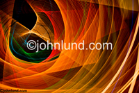 Concept stock photo of abstract light patterns in intricate and complex geometric forms indicating science, mystery and mathematics. Bold Orange Gold and Yellow lights with a touch of green. Photographs of swirling light patterns on black.