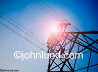 Stock Photo looking up at high tension power lines silhouetted against the sun in a symbol of energy, resources and power. Picture of power lines.