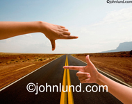 Concept stock photo of a pair of hands framing a road symbolizing a journey, a goal, the way forward and the future.