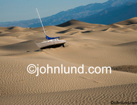 Picture of a sail boat beached in the desert, stranded in an evironmental disaster, an ecological nightmare and due to global warming. Picture of a sailboat in the desert.