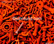Stock photo of a shiny bolt among rusty nuts and bolts, ball bearings, chainlinks and washers. One new bolt in a pile of old and rusty nuts and bolts, ball bearings and washers.
