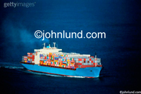 Picture of a fully loaded container cargo ship with flags of many countries on the sides of the containers.