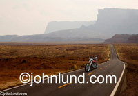 Stock photo of a lone motorcycle rider on a long stetch of deserted road riding on a journey to freedom and possibilities.