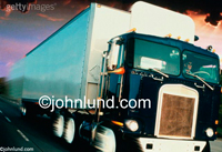 A speeding semi truck fills the frame as it speeds its cargo onwards down the highway in a stock photo about transportation and commerce.