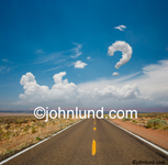 A cloud forms a question mark over a long road disappearing into the distance illustrating a journey, a trip, and self discovery. Interesting cloud pics.