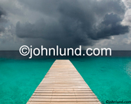 Stock photo of a wooden pier in the tropics with a storm coming in over the warm blue waters, photographed in Bonaire.