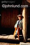 Stock Photo of a young (six years old) cowboy wearing a cowboy hat and chaps as he leans noncholantly against a post.