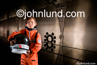 Picture of a young female astronaut holding a helmet and wearing a space suit while standing in a space station or high tech environment. Space suit pics.