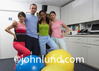 Photo of the physical therapy staff or maybe just and exercise class. It's your choice. Colorful photo for ads showing a multi-ethnic group of people wearing brightly colored clothing and standing with a bunch of bright colored exercise balls.