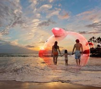 A piggy bank is superimposed over a family at the beach in a stock photo about saving for family vacations.