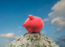 A piggy bank sits atop a huge pile of cash under a summer sky in a stock photo about savings, investment, banking and finance.