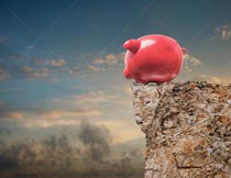 A piggy bank stands at the edge of a cliff in a funny stock photo about risks and dangers in saving and investing.