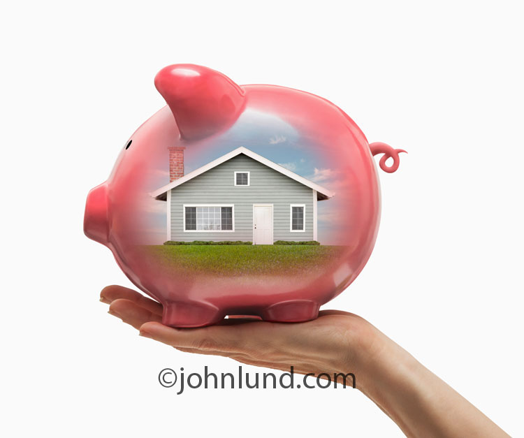 The piggy bank being held up by a hand in this photo has a home visible within in a metaphor for home mortgage finance, savings and investments.