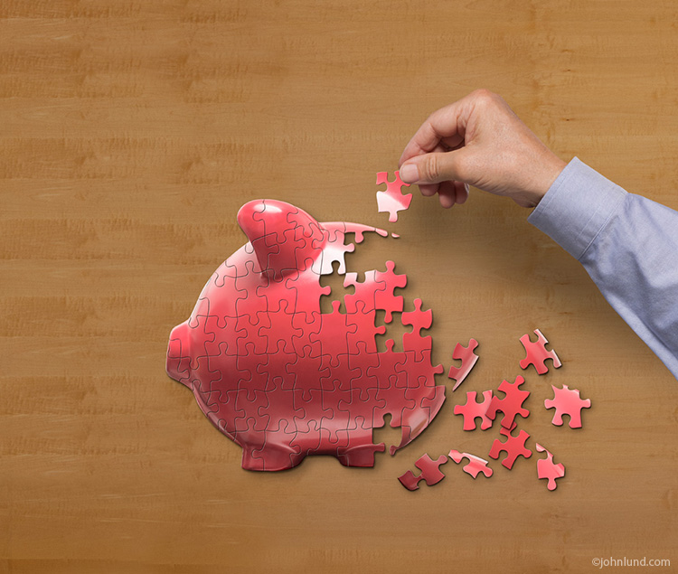 A hand puts a piggy bank jigsaw puzzle piece into place in an image about investment strategy, planning, and issues.