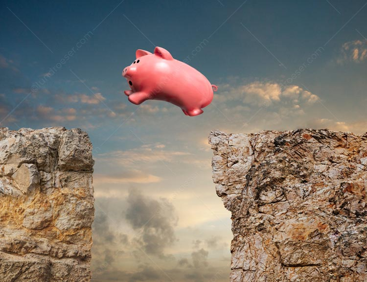 A piggy bank leaps from one cliff to another in a stock photo about financial risk and opportunity, about taking an investment leap.