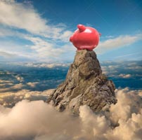 A piggy bank sits atop a mountain peak high above the clouds in a stock photo about financial and investment success.