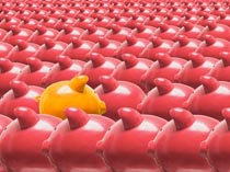 A gold piggy bank stands out from the crowd in a stock photo of pink piggy banks with one gold piggy bank facing the opposite direction.