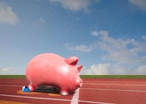 A piggy bank is in the starting blocks in a stock photo about quick starts and competition in savings and investment.