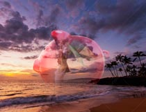 A piggy bank is superimposed over a senior woman enjoying a tropical sunset in a stock photo about financial and retirement planning success.
