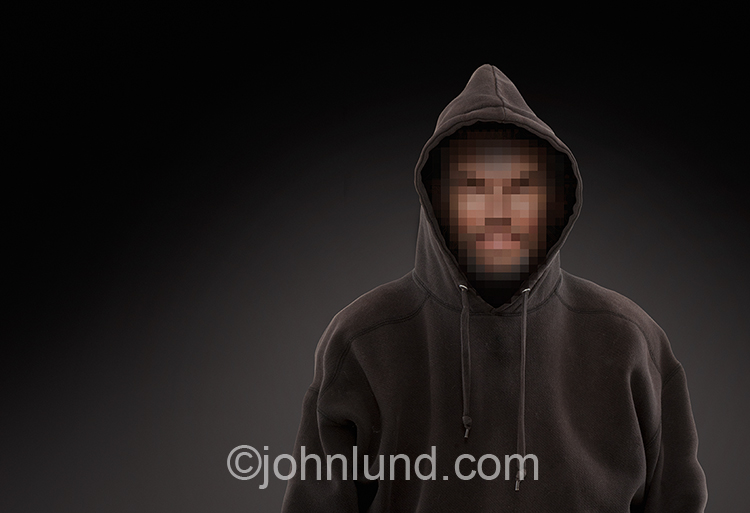 In this stark and chilling stock photo a cyber criminal hacker wearing a hoodie has a face concealed by pixelation and a message of the sinister and evil nature of hackers intent on spreading malware, ransomware and spam as they attempt to steal intellect