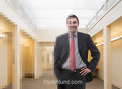 A businessman stand in an office in this stock photo in which half the photo has been turned into pixels symbolizing the merging of the real and the digital worlds and the move to online and cloud computing in the business world.