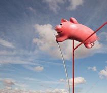 A piggy bank pole vaults over a high bar in a stock photo about savings, investment and financial success.