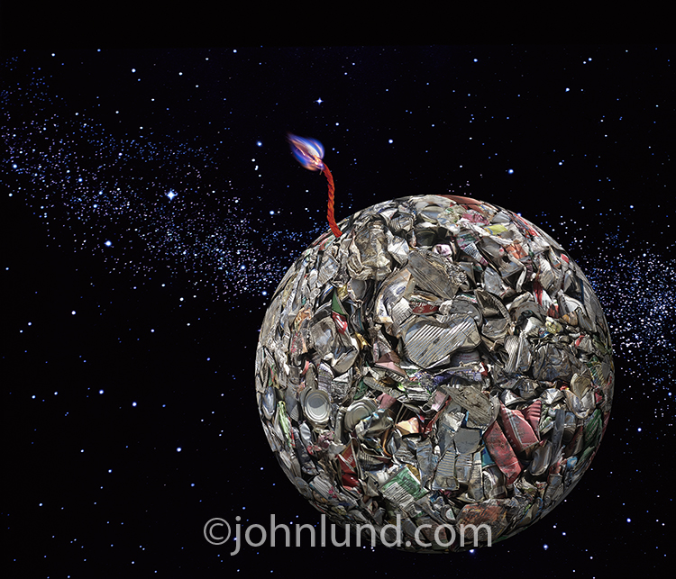 The dangers and risks of pollution to our planet are dramatically displayed in this image of a planet-like sphere of smashed cans and garbage floating in outer space with a lit fuse providing evidence of the impending explosion of doom!
