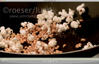 Slow motion video featuring a frying pan of hot oil and popping popcorn kernels blasting up and out in a hiss of steam.