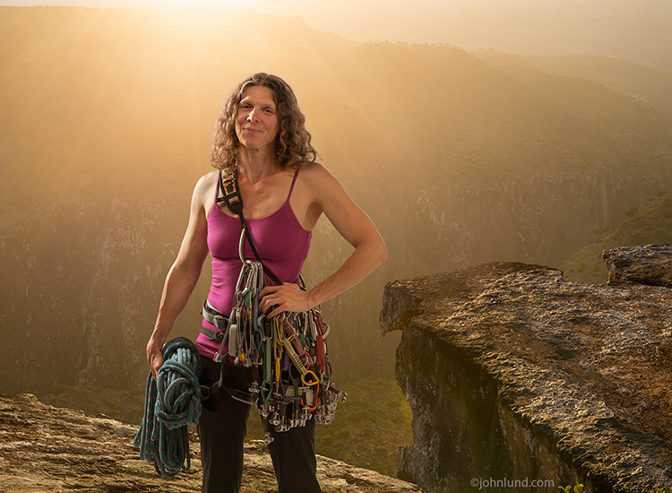 In this portrait a fit and strong woman rock climber stands, in her climbing gear (including a rope and carabiners), before a cliff during a golden sunset in an image about confidence, capability and role models for women.