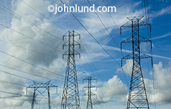 Power lines and pylons stretch across the frame below a cloud filled sky in this stock image about energy, power, transmission and infrastructure.