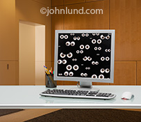 Hackers, cyber criminals, social media exposure and more are illustrated in this image of a computer monitor filled with eye balls and situated in a high end office setting.