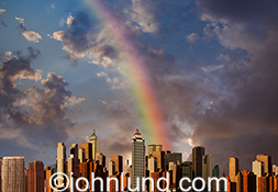 A rainbow arches over a city skyline in a stock photo about success and opportunity.