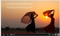 HD video of camels and women in saris silhouetted against a sunset as they walk across the desert sand dunes.