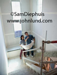 Young couple visiting their new home that is still under construction. The couple is standing in the stair well and pointing up to the top.  Happy new home buyers with blueprints. Sheet rock has been put up.