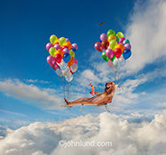 A Bloodhound sips a tropical drink as he floats over the clouds in a lounge chair held aloft by colorful clusters of balloons in a humorous stock photo about retirement.