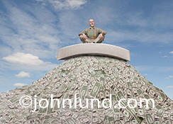 Retirement investing is the primary concept behind this stock image of a senior man sitting on a mattress that in turn sits high up on mountain of money in the form of dollar bills.