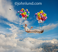 Retirement: A senior man floats through the clouds on a lounge chair supported by balloons in a concept photo about retirement issues, retirement investing and leisure activities.