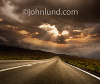 In this photo of a long straight road disappearing into a distant mountain range the sun fights to break out of storm clouds and casts rays down illuminating the way forward.