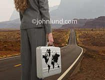 A woman stands on a long road holding a briefcase with a world atlas illustrated on its side in a metaphorical image about the long road to success and Global commerce.