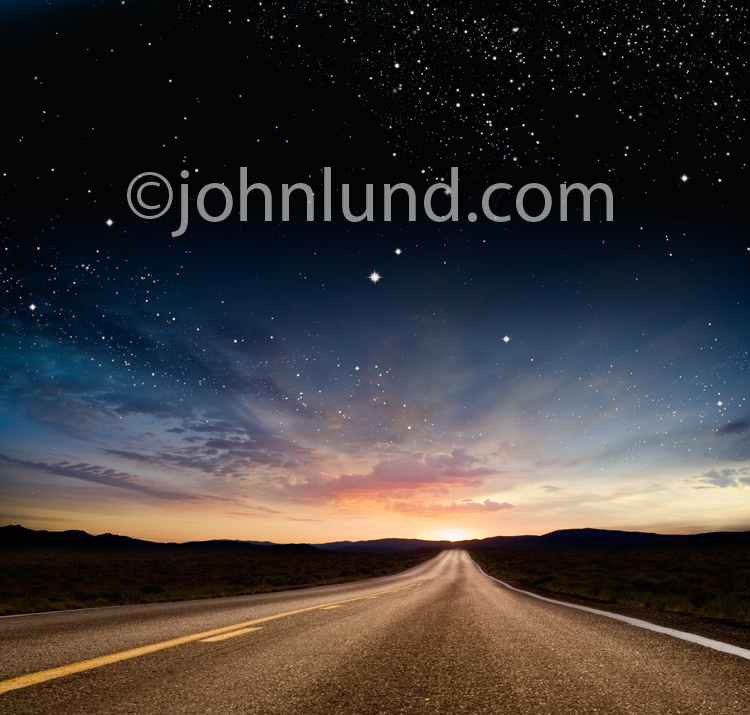 A long road stretches into the sunrise as a magical dawn sky of staries unfolds above in a stock photo about the journey, the way forward, and the promise of the future.